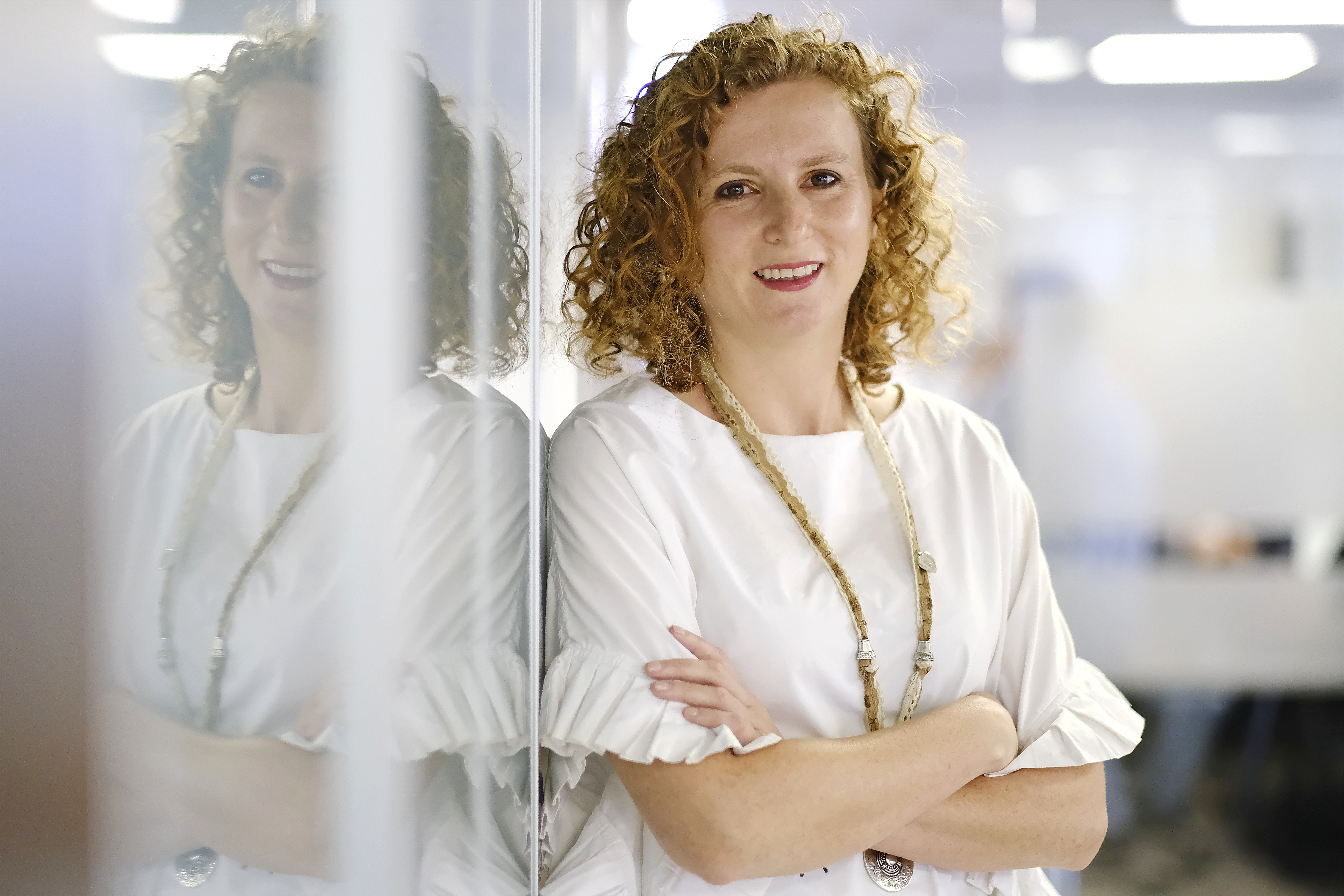 A woman with red curly hair leans smiling against a wall